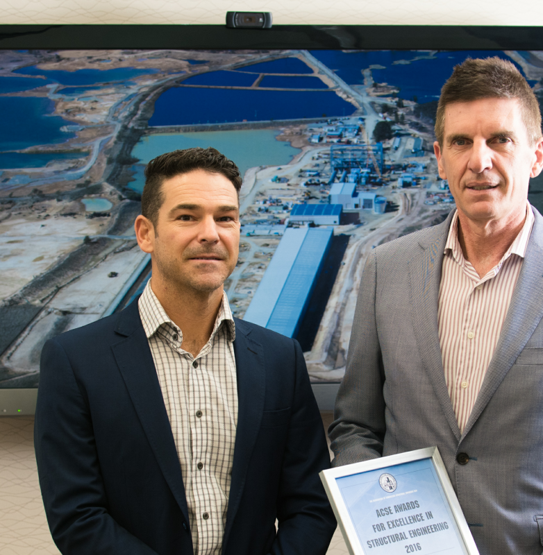 Grant Roe, BE(Hons) MEngSc MBA MIEAust CPEng NER, managing director of Costin Roe Consulting [right], and Mark Wilson, B Eng (Civil) B Surv ME CPEng, director of Costin Roe Consulting [left], with ACSE NSW 2016 award and aerial view of the Veolia Woodlawn MBT facility site near Goulburn, NSW